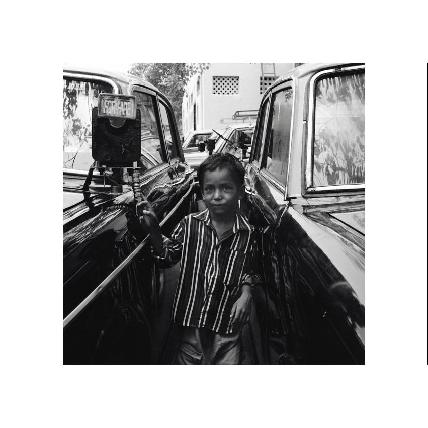 Jeune garcon de Mumbay posant entre deux taxis